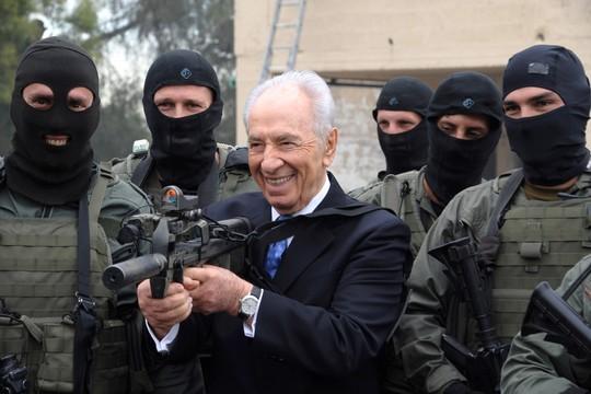 """President Shimon Peres visits Border Police's counterterrorist unit's base. Photo: President Peres' fire power display with soldiers of the unit.  áé÷åø ðùéà äîãéðä ùîòåï ôøñ ááñéñ äéçéãä äîéåçãú ììåçîä áèøåø (éî""""î) ùì îùîø äâáåì. öéìåí: äðùéà ôøñ áîôâï ëç...àù òí ìåçîé äéçéãä."""