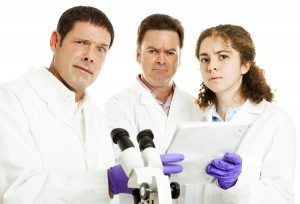 Perplexed confused scientists looking at lab results. White background.